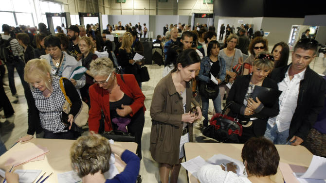 Plaintiffs register as they arrive at the Parc Chanot temporary courthouse in Marseille, Southern France, to attend the trial of Jean-Claude Mas, who founded and ran breast implant-maker Poly Implant Prothese, Wednesday, April 17, 2013.  Hundreds of women who received faulty breast implants are gathering in the south of France to witness the fraud trial of five executives accused of using cheap industrial silicone to fill tens of thousands of implants around the world.  The now-defunct company exported to more than 60 countries and was one of the world's leading implant makers. (AP Photo/Claude Paris)