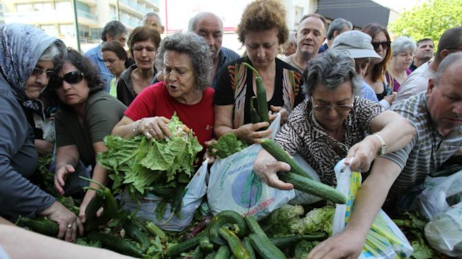People reach out for fresh produce distributed by Greek street fruit and vegetable market vendors during a protest in Athens, Wednesday, May 15, 2013. The union of Greek farmers markets went on strike, Wednesday, as protesters set up stands and started distributing vegetables to a fast growing crowd. The market vendors are the latest professional group in Greece to protest a sweeping market liberalization drive demanded by rescue creditors,  and timed their protest to draft legislation due to be voted in parliament to implement the new guidelines. (AP Photo/Thanassis Stavrakis)