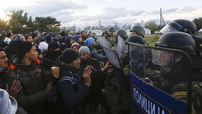 Migrants push a line of Macedonian police officers as they try to cross the Greek-Macedonian border near the Greek village of Idomeni