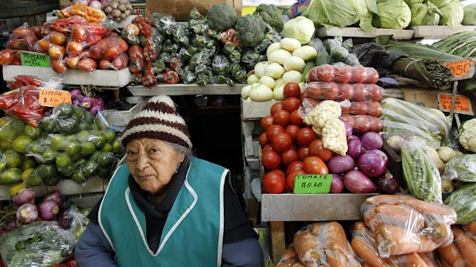 A woman sits at her vegetable stand at a market in downtown Quito, Ecuador, Thursday, June 27, 2013. Unlike with China, Russia or Cuba, countries where the U.S. has relatively few tools to force Edward Snowden's handover, the Obama administration could swiftly hit Ecuador in the pocketbook by denying reduced tariffs on cut flowers, artichokes and broccoli if it grants Snowden's request for asylum. Those represent hundreds of millions of dollars in annual exports for this country where nearly half of foreign trade depends on the U.S. (AP Photo/Dolores Ochoa)