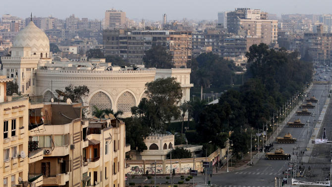 "View of the presidential palace guarded by military tanks in Cairo, Egypt, Sunday, Dec. 16, 2012. Key Egyptian rights groups called Sunday for a repeat of the first round of the constitutional referendum, alleging the vote was marred by widespread violations. Islamists who back the disputed charter claimed they were in the lead with a majority of ""yes"" votes. (AP Photo/Hassan Ammar)"
