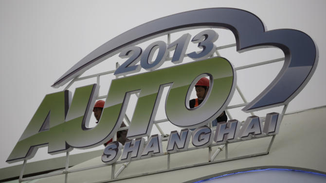 Workers install a sign ahead of the Shanghai International Automobile Industry Exhibition (AUTO Shanghai) at the Shanghai International Exhibition Center in Shanghai, China Thursday, April 18, 2013.  These should be good times for Chinese automakers as they prepare to show off their latest models at the Shanghai auto show. Their home market is the world's biggest and growing. But independent automakers such as Chery and Geely are being squeezed by bigger, richer global rivals including General Motors and Nissan that are creating low-priced models for local tastes. Domestic brands account for less than half of their own market. (AP Photo/Eugene Hoshiko)