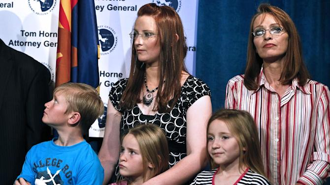 Ruby Jessop, rear left, and sister Flora Jessop, rear right, stand with Ruby's children as they listen as Arizona Attorney General Tom Horne during a news conference, Tuesday, Jan. 22, 2013, in Phoenix.  Horne discussed how his agency and others helped Ruby and her six children leave a polygamist sect along the Utah-Arizona border.(AP Photo/Ross D. Franklin)
