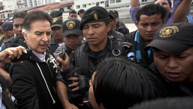 Former president of Guatemala, Alfonso Portillo, left, speaks to the press as he is led by police to an aircraft that will fly him to the United States from Guatemala City, Friday, May 24, 2013.  Portillo was extradited to the United States to face charges of laundering $70 million in Guatemalan funds through U.S. bank accounts. (AP Photo)