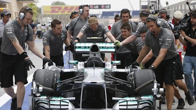 Mercedes mechanics push the car of Lewis Hamilton of Britain during the third practice session of the Bahrain Formula One Grand Prix at the Bahrain International Circuit in Sakhir, Bahrain, Saturday, April 20, 2013. The Bahrain Formula One Grand Prix will take place on Sunday. (AP Photo/Kamran Jebreili)