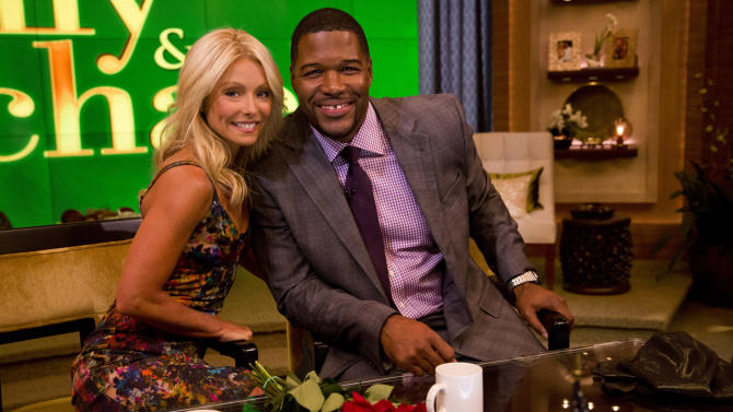 """Former football player Michael Strahan, right, poses Kelly Ripa on the set of the newly named """"Live! with Kelly and Michael"""" on Tuesday, Sept. 4, 2012 in New York. Strahan joined the popular morning show as a permanent co-host on Tuesday, fulfilling a joking prophecy he made to Regis Philbin more than four years ago. The gap-toothed former New York Giant jogged onto the morning show set and picked up co-host Kelly Ripa in a bear hug, lifting her off her feet. He replaces Philbin, who left last November. Strahan was the survivor in a series of on-air tryouts of potential co-hosts since Philbin left, and his hiring has been an open secret for the past two weeks. (Photo by Charles Sykes/Invision/AP Images)"""