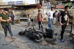 People gather at the site of suicide blasts in Bag …