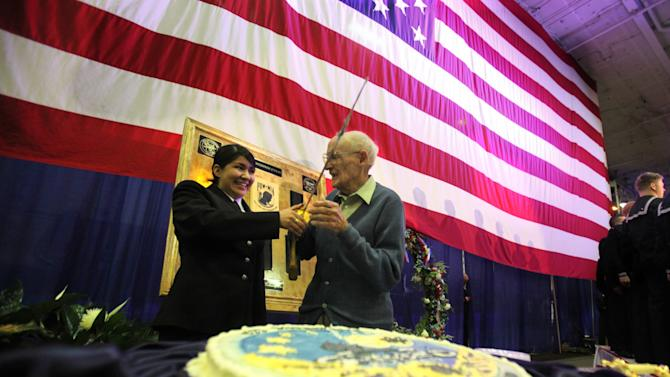 Seaman Tzitlali Rivero, 18, left, the youngest sailor in the Enterprise crew, and original crew member Billy Angeroth, 93, get ready to cut the cake as the aircraft carrier USS Enterprise celebrates its 50th birthday at Naval Station Norfolk on Monday, Nov. 28, 2011.  (AP Photo/The Virginian-Pilot, Steve Earley)