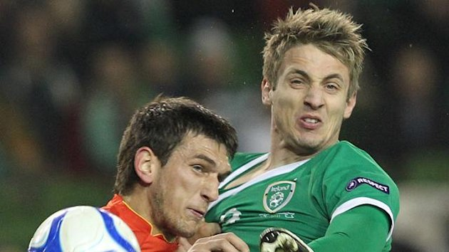 Ireland's Kevin Doyle (R) vies for the ball with Macedonia's Goran Popov (L)