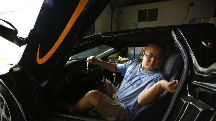 Li sits in a handmade replica of Lamborghini Diablo as he and Wang prepare for a test drive at a garage on the outskirts of Beijing