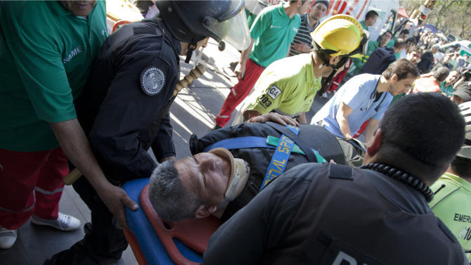 Police officers and paramedics carry a wounded passenger to an ambulance after a commuter train slammed into the end of the line when arriving to Once central station early this morning in Buenos Aires, Argentina, Saturday, Oct. 19, 2013. Paramedics rescued scores of wounded commuters. According to Security Secretary Sergio Berni, they are still evacuating the wrecked train, making that impossible to say immediately why the train failed to stop, crashing through the bumper at the end of the line. (AP Photo/Eduardo Di Baia)
