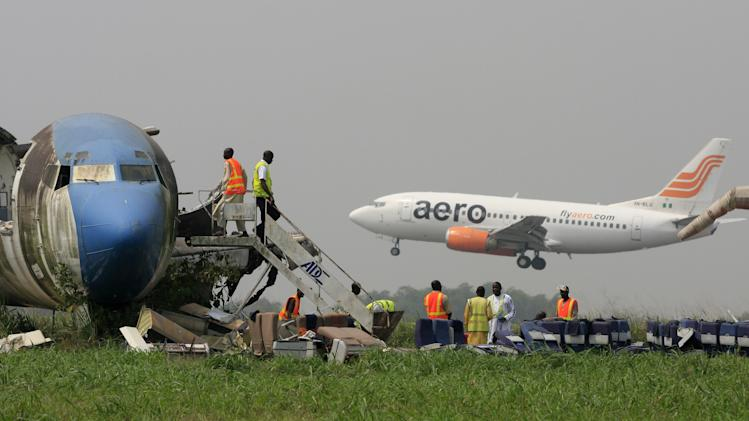A passenger plane lands as workers dismantle an abandoned aircraft at Murtala Muhammed International Airport in Lagos, Nigeria, Thursday, Jan. 31, 2013. Nigerian aviation officials have begun trying to dismantle and remove the hulks of abandoned airplanes from airports around the country. Officials say there are least 65 abandoned planes at the country's airports, with at least 13 at Lagos' international airport. (AP Photo/Jon Gambrell)