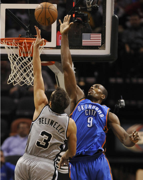 Oklahoma City Thunder forward Serge Ibaka, right, defends San Antonio Spurs guard Marco Belinelli, of Italy, during the second half of an NBA basketball game, Saturday, Dec. 21, 2013, in San Antonio.