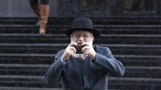 An Amish man pretends to take a photo of the media as he leaves the U.S. Federal courthouse Friday, Feb. 8, 2013, in Cleveland. Sam Mullet Sr., 67, the ringleader in a series of unusual hair- and beard-cutting attacks on fellow Amish religious followers in the U.S. was sentenced Friday to 15 years in prison, and 15 family members received sentences of one year to seven years. The defendants were charged with a hate crime because prosecutors believe religious differences brought about the attacks. (AP Photo/Tony Dejak)
