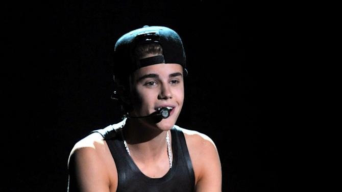 FILE - In this Nov. 18, 2012 file photo, Justin Bieber performs at the 40th Anniversary American Music Awards, in Los Angeles. Los Angeles police announced Tuesday Dec. 18, 2012 that they have arrested an unidentified juvenile for sending hoax messages that led to large police responses to the homes of Ashton Kutcher and Justin Bieber. (Photo by John Shearer/Invision/AP, File)
