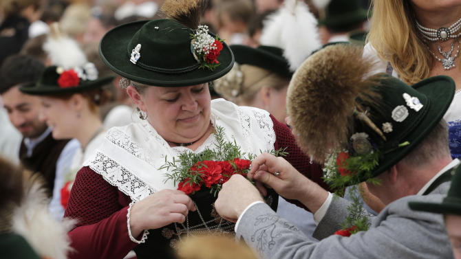 People in traditional Bavarian clothes prepare their costumes after the Oktoberfest parade at the second day of the 181st Oktoberfest beer festival in Munich, southern Germany, Sunday, Sept. 21, 2014. The world's largest beer festival will be held from Sept. 20 to Oct. 5, 2014. (AP Photo/Matthias Schrader)