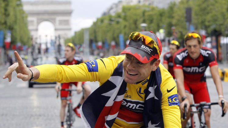 Tour de France winner Cadel Evans of Australia, wearing the overall leader's yellow jersey, cycles down the Champs Elysees during the victory parade after winning the Tour de France cycling race in Paris, France, Sunday July 24, 2011.  (AP Photo/Laurent Cipriani)
