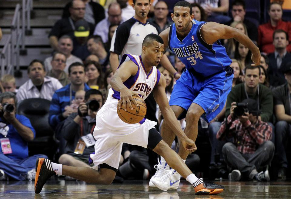 Phoenix Suns' Sebastian Telfair, left, stops his drive against Dallas Mavericks' Brandan Wright (34) during the first half of an NBA basketball game, Thursday, Dec. 6, 2012, in Phoenix. (AP Photo/Matt York)