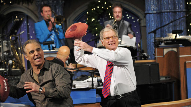 """In this photo released by CBS, host David Letterman, right, and comic Jay Thomas get ready to throw footballs at the Late Show Christmas tree during the annual Late Show Holiday Quarterback Challenge on the set of """"Late Show with David Letterman,"""" airing Thursday, Dec. 23, 2011 on the CBS Television Network.  Thomas and Letterman each take turns tossing footballs at the Late Show Christmas tree to try and knock off the giant meatball perched at its top.   (AP Photo/CBS, John Paul Filo)"""