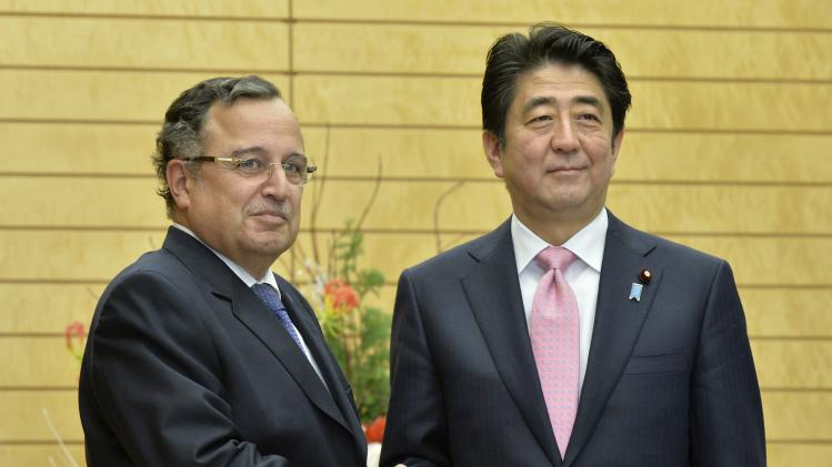 Egypt's Foreign Minister Nabil Fahmy shakes hands with Japan's Prime Minister Shinzo Abe in Tokyo