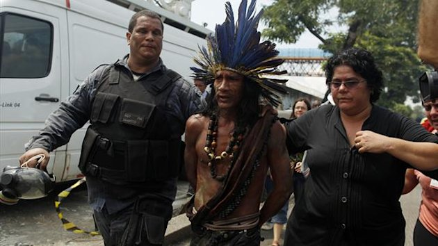 Riot police lead away an Amazon native (Reuters)
