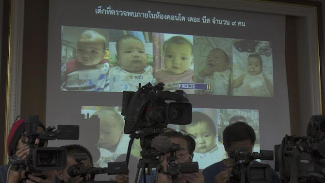 """In this Tuesday, Aug. 12, 2014 photo, Thai police display pictures of surrogate babies born to a Japanese man who is at the center of a surrogacy scandal during a press conference at the police headquarters in Chonburi, Thailand. Interpol said Friday it has launched a multinational investigation into what Thailand has dubbed the """"Baby Factory"""" case: the 24-year-old Japanese businessman who has 16 surrogate babies and an alleged desire to father hundreds more. Police raided a Bangkok condominium earlier this month and found nine babies and nine nannies living in a few unfurnished rooms filled with baby bottles, bouncy chairs, play pens and diapers. They have since identified Mitsutoki Shigeta as the father of those babies - and seven others. (AP Photo/Sakchai Lalit)"""