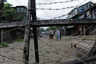 Muslim Rohingyas are seen walking towards a barbed wire fence along a road in the Aung Mingalar district of Sittwe on October 12. Surging sectarian violence in western Myanmar has left at least 64 people dead and scores more wounded, a local official says, casting a shadow over the government&#39;s reform drive