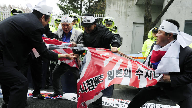 South Korean protesters tear a Japanese wartime flag during a rally to protest Japanese lawmakers's visit to Yasukuni Shrine in Tokyo, in front of the residence of Japan's ambassador in  Seoul, South Korea, Tuesday, April 23, 2013. Dozens of Japanese lawmakers paid homage at the national war shrine Tuesday morning, risking more anger from neighbors South Korea and China over visits they see as failures to acknowledge Japan's militaristic past. (AP Photo)