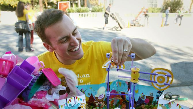 FILE - In this Jan. 13, 2014, file photo, Beau Lewis, GoldieBlox chief marketing officer, puts together a Goldie Blox's Spinning Machine toy set, in Pasadena, Calif., before a film crew films a commercial for his company. GoldieBlox won last year's Intuit Small Business Big Game competition in which small companies vied for a 30-second spot during Super Bowl 49. The software maker is planning its second competition, which will begin June 1, 2015. (AP Photo/Nick Ut, File)