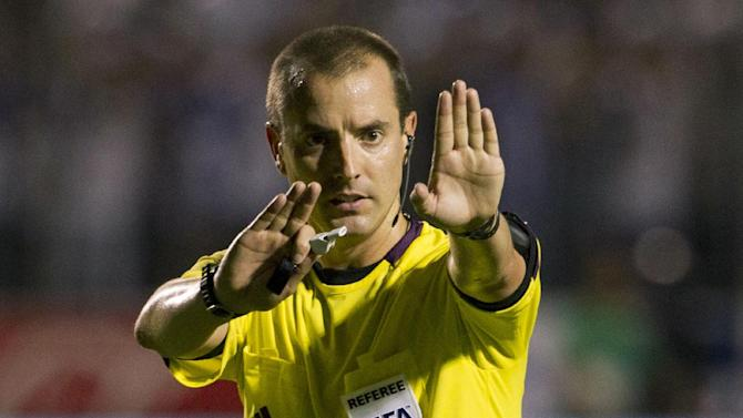 FILE - In this Tuesday Sept. 10, 2013 file photo, referee Mark Geiger signals a call at a 2014 World Cup qualifier soccer match between Honduras and Panama in Tegucigalpa, Honduras. Mark Geiger aims to become the first American referee to advance from the group stage in the World Cup in Brazil. (AP Photo/Moises Castillo, File)