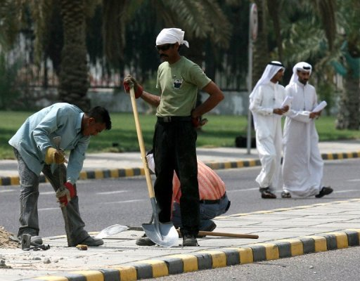 Asian labourers work in a street in Kuwait City on September 10, 2008. Kuwait, where expats make up 68 percent of the population, plans to reduce the number of foreigners living in the Gulf state by one million over the next decade, a minister said on Tuesday