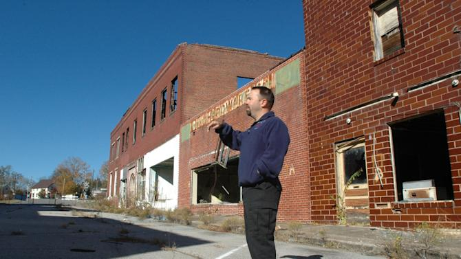 In this Tuesday, Nov. 13, 2012 photo, Cordova, Ala., Fire Chief Dean Harbison gestures as he discusses the town's tornado-damaged downtown. The area looks much as it did right after tornadoes struck in April 2011 because the Federal Emergency Management Agency has yet to provide funding for demolition and the city can't afford to do the work itself. (AP Photo/Jay Reeves)