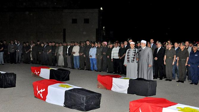 FILE - In this Wednesday, Nov. 20, 2013 file image released on the official Facebook page of the Egyptian Military Spokesman of the Armed Forces, Egyptian Defense Minister Gen. Abdel-Fattah el-Sissi, second row third right, prays with relatives of 2nd Field Army soldiers who were killed after a suicide bomber rammed his explosive-laden car into one of two buses carrying off-duty soldiers, at the road between the border town of Rafah and the coastal city of el-Arish, during their funeral procession in Cairo, Egypt. In Egypt, misery just keeps piling and, fittingly, the nation is officially in mourning. Political violence and unrest have plagued Egypt since the ouster in 2011 of longtime authoritarian ruler Hosni Mubarak, but a flurry of deadly incidents this week appears to have touched a raw nerve in the nation's psyche, with many Egyptians abandoning hopes for democracy and freedom and instead embracing a grim view of the future. (AP Photo/The Official Facebook Page of the Egyptian Military Spokesman of the Armed Forces, File)