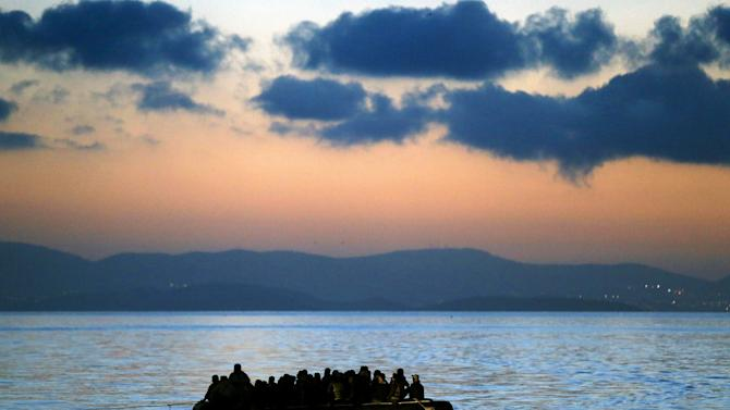 A dinghy overcrowded with immigrants is towed by a Greek coast guard patrol boat into the port on Kos