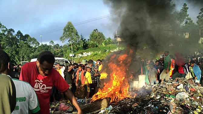 FILE - In this Feb. 6, 2013 file photo, bystanders watch as a woman accused of witchcraft is burned alive in the Western Highlands provincial capital of Mount Hagen in Papua New Guinea.  Papua New Guinea police charged two people on Monday, Feb. 18, 2013,  with the grisly killing of a woman who was burned alive in front of hundreds of people, including young children, after being accused of witchcraft.(AP Photo/Post Courier, File) PAPUA NEW GUINEA OUT