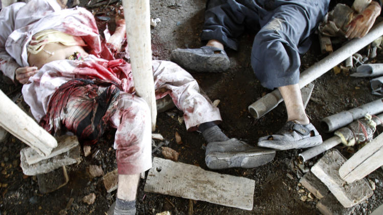 The bodies of alleged militants are seen on the ground after a gun battle in Kabul, Afghanistan, Monday, April 16, 2012. A brazen, 18-hour Taliban attack on the Afghan capital ended early Monday when insurgents who had holed up overnight in two buildings were overcome by heavy gunfire from Afghan-led forces and pre-dawn air assaults from U.S.-led coalition helicopters. (AP Photo/Ahmad Jamshid)