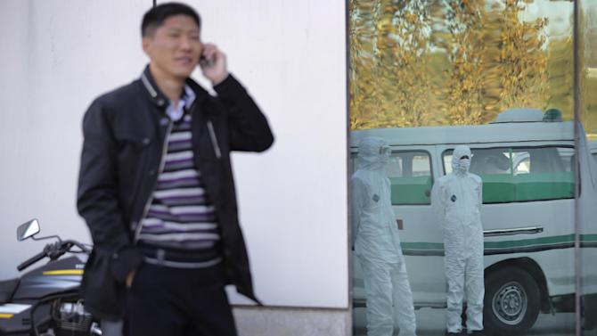 This Monday, Oct. 27, 2014 photo shows a North Korean man speaking on his mobile phone as medical personnel dressed in protective suits wait by an ambulance, at the Sunan International Airport, in Pyongyang, North Korea. North Korea would seem like the last place on Earth that has anything to worry about from Ebola. But it's virtually gone on DefCon 1 over what it sees as a looming invasion from the outside world that threatens to infiltrate its borders and relentlessly attack its people unless dramatic measures are taken immediately. It has banned tourists, put business groups on hold and is looking even more suspiciously than usual at every foreign face coming across its borders. (AP Photo/Wong Maye-E)