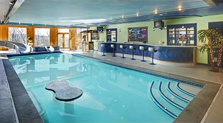 Features An Indoor Pool With Slide Conveniently Situated Next To A Bar