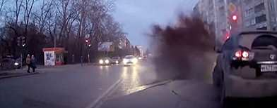 A car camera captures the moment a road buckles due to a water main break, causing a minor accident.