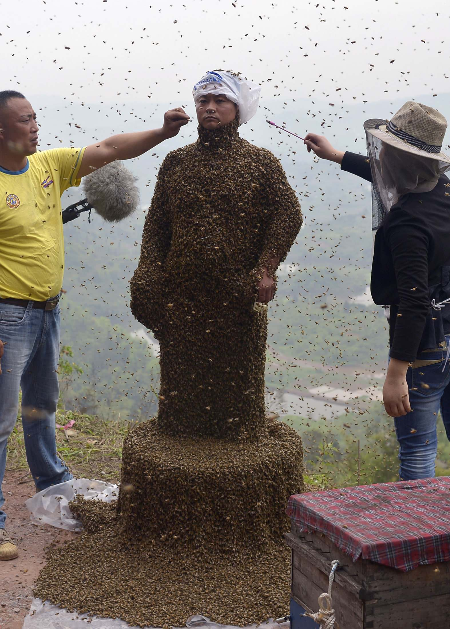 Assistants use burning incense and cigarettes to drive bees away from the face of She Ping. (Reuters/China Daily)