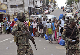 Liberian soldiers scan people for signs of the Ebola virus, as they control people from entering the West Point area in the city of Monrovia, Liberia, Saturday, Aug. 23, 2014. (AP Photo/Abbas Dulleh)