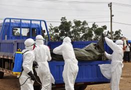 Health workers load the body of a man found on the street, suspected of dying from the Ebola virus, in the capital city of Monrovia, Liberia, Tuesday, Aug. 12, 2014. (AP Photo/Abbas Dulleh)