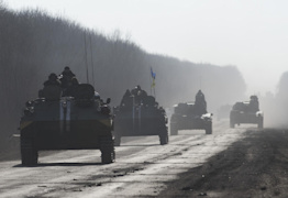 Ukrainian troops ride on an armored vehicles ahead of self-propelled artillery near Artemivsk, eastern Ukraine, Monday, Feb. 23, 2015. A Ukrainian military spokesman says continuing attacks from rebels are delaying Ukrainian forces' pullback of heavy weapons from the front line in the country's east. (AP Photo/Evgeniy Maloletka)