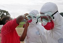 A health worker assists a colleague with his protective gear, as they collect the body of a man suspected to have died from the ebola virus, in Monrovia, Liberia, Tuesday, Aug. 12, 2014. (AP Photo/Abbas Dulleh)