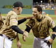 Pittsburgh Pirates &#39; Russell Martin (55) is congratulated by coach Dave Jauss after Houston Astros shortstop Jake Elmore, and right fielder Jimmy Paredes collided as they tried to catch a pop fly by ...
