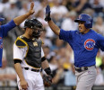 Pittsburgh Pirates catcher Russell Martin, center, waits as Chicago Cubs' Darwin Barney, right, is greeted by teammate Welington Castillo, left, after both scored on a double by Cubs starting ...