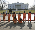 FILE - In this Jan. 14, 2011, file photo human rights activists, hooded and wearing orange prison garb to represent prisoners at Guantanamo Bay , Cuba, demonstrate in front of the White House in ...