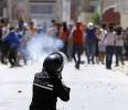 A riot police officer fires teargas during clashes with supporters of Islamist group Ansar al-Sharia at Hai al Tadamon in Tunis