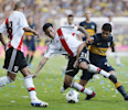 River Plate&#39;s Leonel Vagioni, center, fights for the ball against Boca Junior&#39;s Lautaro Acosta, right, during an Argentina&#39;s league soccer match in Buenos Aires, Argentina, Sunday, May 5, 2013