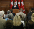 Canada 's PM Harper receives a standing ovation while delivering a speech during a Conservative caucus meeting on Parliament Hill in Ottawa